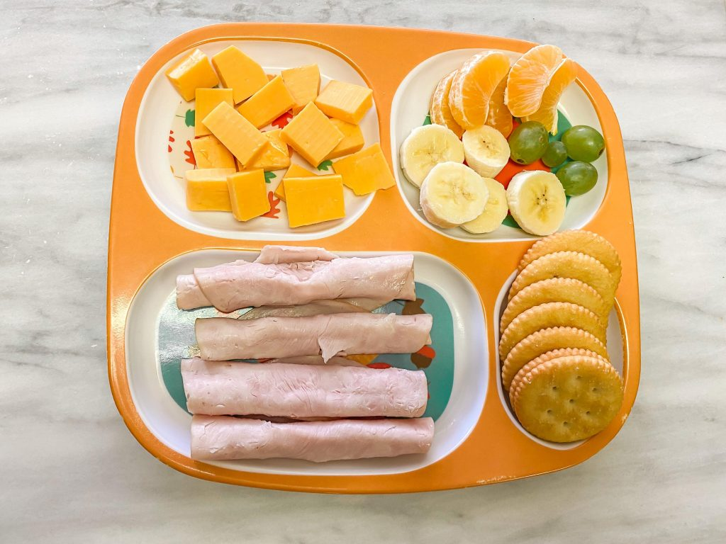 At home Lunchable. Lunch meat, crackers, cheese cubes and fresh fruit.